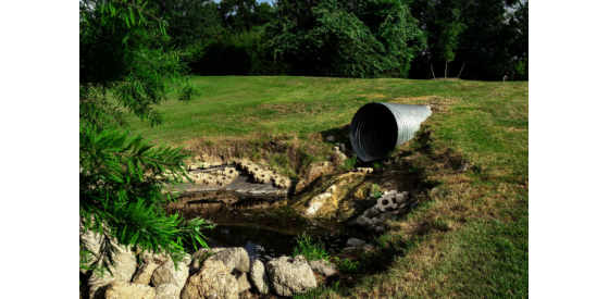 Dirty water flowing from pipe into stream