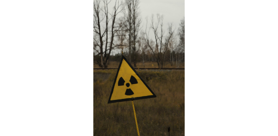 radiation sign on pole in the middle of a field