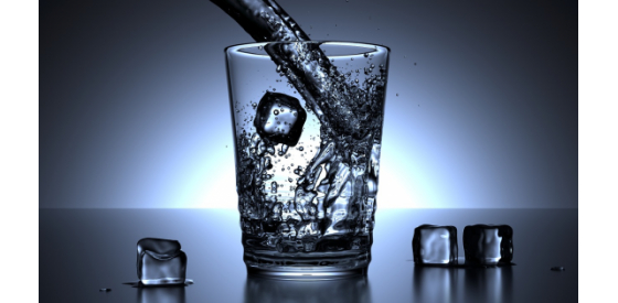 Water pouring into a glass of water full of ice cubes