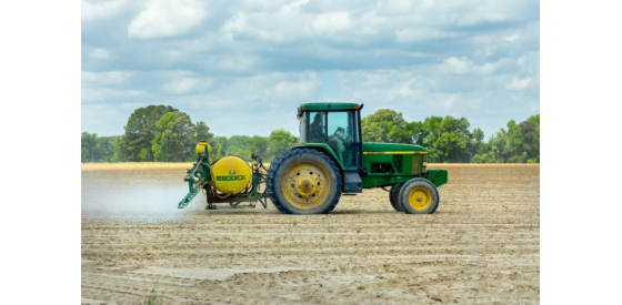 Tractor spraying farm with herbicides like Alachlor that can end up in drinking water