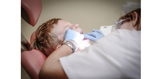 Dentist looking into a child patient's mouth to check his teeth