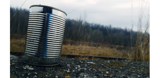 Aluminium can on a street with natural scenery in the background.