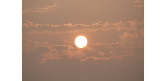 Sun setting over clouds