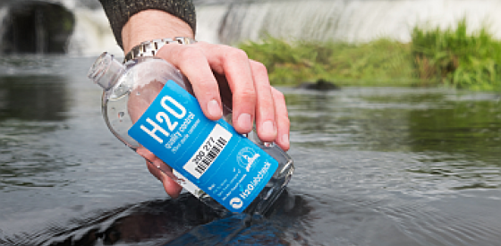 Hand pouring river water into sampling bottle