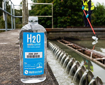 H2O Quality Control Bottle for wastewater assessment, wastewater treatment reservoir in the background