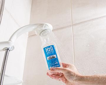 Hand holding Water sampling bottle under showerhead