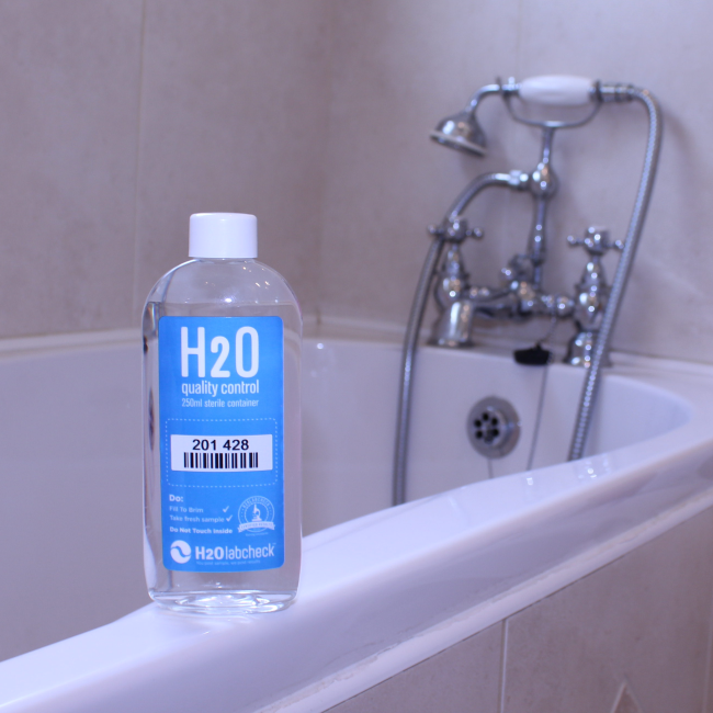H2Olabcheck sampling bottle, bathroom on the background