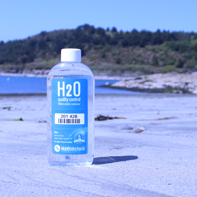 Water sampling bottle on the front, beach on the background