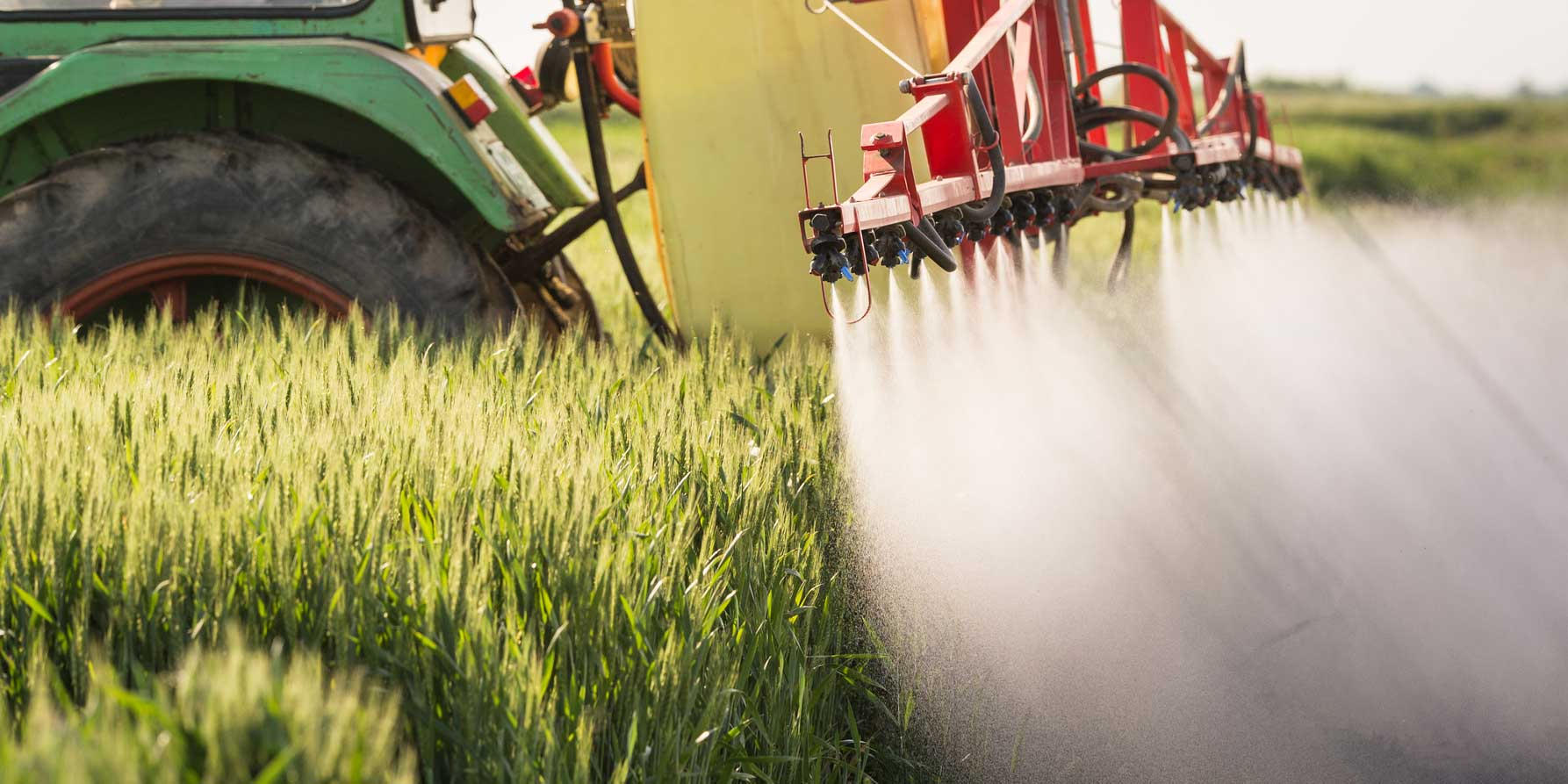 Agricultural machinery spreading pesticides on crops